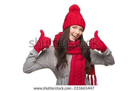Closeup of happy woman wearing red warm winter hat, scarf and gloves giving you double thumb up, over white background - stock photo