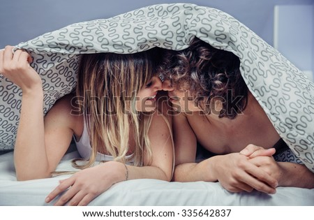 Closeup of happy young couple in love kissing under a duvet cover. Love and couple relationships concept. - stock photo