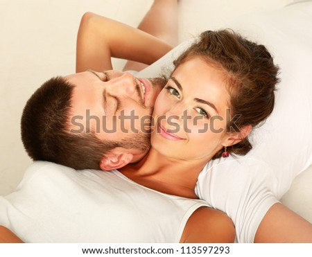 Closeup of happy young couple lying on floor. Top view - stock photo