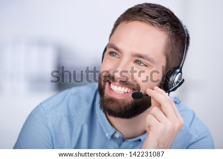 Closeup of happy young customer service executive communicating on headset in office - stock photo