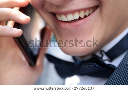 Closeup of healthy clean teeth in open male lips in beautiful smile on young emotional joyful shaven face of guy in black bow tie on white collar holding cellphone and speaking, horizontal photo - stock photo