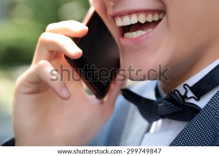 Closeup of healthy clean teeth in open male mouth in pretty smile on young emotional laghing shaven face of boy in black bow tie on white collar holding mobile phone and talking, horizontal photo - stock photo