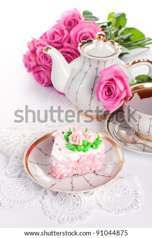 Closeup of heart-shaped cake with roses and cup of tea - stock photo