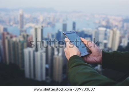 Closeup of hipster guy is checking e-mail on smart phone, while is standing on last skyscraper floor with view of New York cityscape on cold foggy day. Young male connecting to internet via cellphone - stock photo