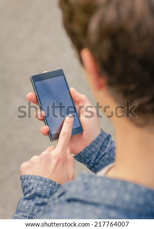 Closeup of hipster teenager using a smart phone with his hand outdoors - stock photo