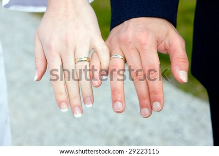 Closeup of holding man's and woman's hands wearing wedding ring - stock photo