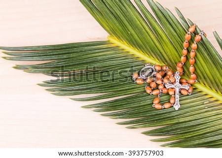 Closeup of Holy Catholic rosary with crucifix and beads on palm leaf - stock photo