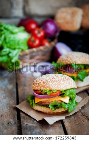 Closeup of home made burgers on wooden background - stock photo