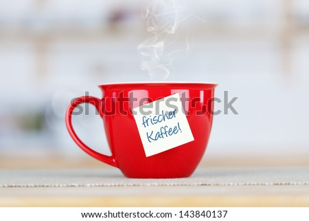 Closeup of hot coffee cup with tag on table in kitchen - stock photo