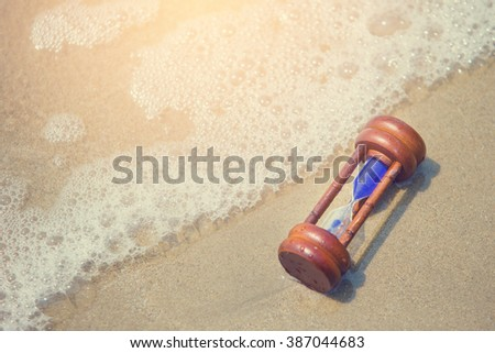Closeup of hourglass on the sand - stock photo