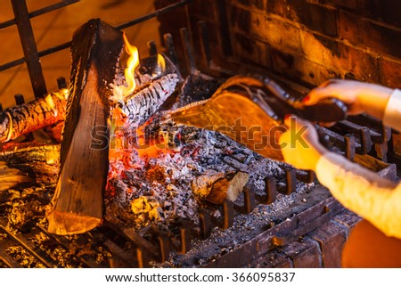 Closeup of human hands at fireplace making fire with bellows. Person heating warming up and relaxing. Winter at home. - stock photo