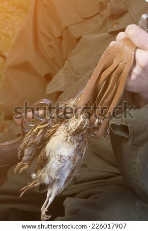Closeup of hunter holding his prey  - stock photo