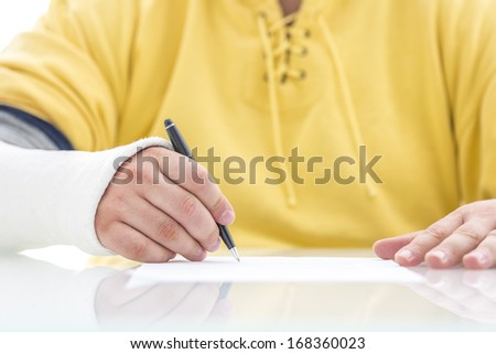Closeup of injured male hand in a cast signing insurance policy claim. - stock photo