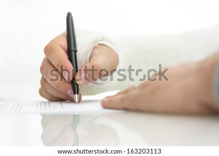 Closeup of injured male hand in a plaster signing insurance or work injury claim. - stock photo