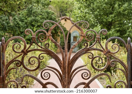 Closeup of iron garden gate with nicely landscaped yard behind it - stock photo