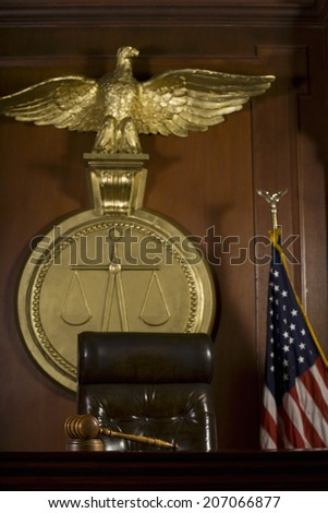 Closeup of judge's seat; bird; gavel and American flag in court room - stock photo