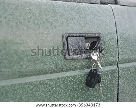 Closeup of keys in a lock of frozen car door, selective focus shot - stock photo