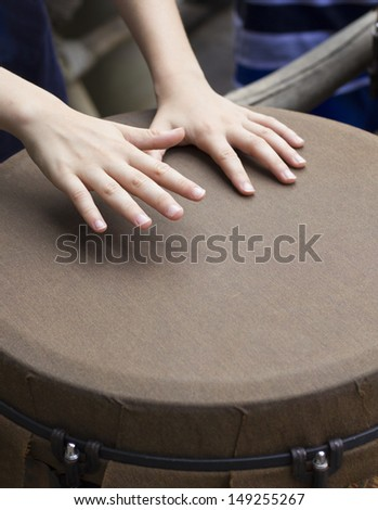 closeup of kid hands playing bongo - stock photo