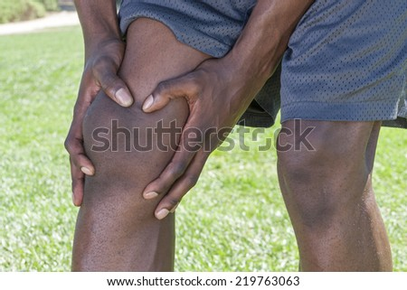 Closeup of knee and leg of lean African American male athlete clutching injured knee with fingers around the patella on green lawn outdoors - stock photo
