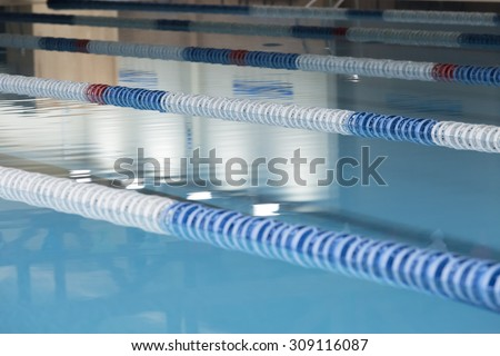 closeup of lane marker buoys in a indoor swimming pool useful as a background - focus on the second buoy - stock photo