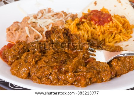 Closeup of Large bite of carne guisada on fork with rice and beans in background.  Shallow dof with selective focus. - stock photo