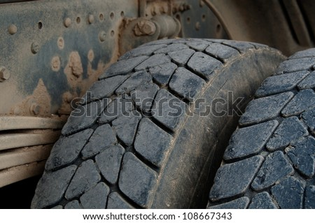 Closeup of large tires and suspension of a dirty dump truck - stock photo