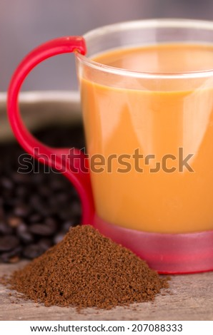 closeup of latte cofffe cup and powder coffee with coffee beans behind selective focus - stock photo