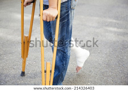 closeup of leg on bandage with crutches - stock photo