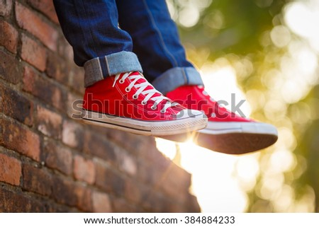 closeup of legs wearing blue jeans and red sneakers - stock photo
