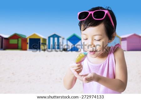 Closeup of little child eats a melt ice cream on the shore while wearing swimwear - stock photo