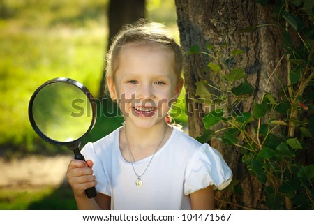 Closeup of little girl with magnifying glass standing near the tree stem outdoors - stock photo