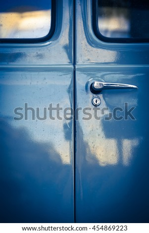 Closeup of locked blue oldtimer car back door with windows, lock and door handle in mysterious vintage light with reflections on it/Ancient Van Door Detail - stock photo