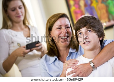 Closeup of loving mother with arm around teenage son smiling - stock photo