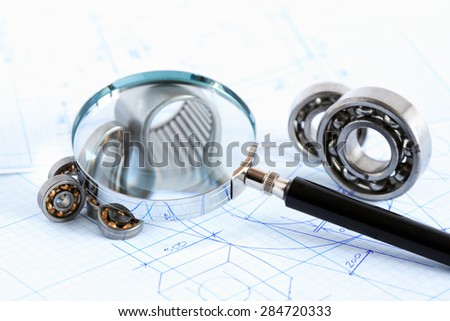 Closeup of magnifying glass near ball bearings on blueprint with draft - stock photo