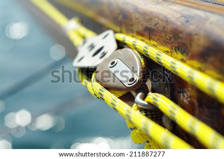 Closeup of mainsheet on old vintage wooden yacht with yellow rope, line used to control the angle of the mainsail to the wind - stock photo