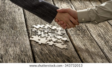 Closeup of male and female business partners shaking hands over a pile of puzzle pieces lying on a textured rustic wooden desk. Conceptual of teamwork and strategy planning. - stock photo