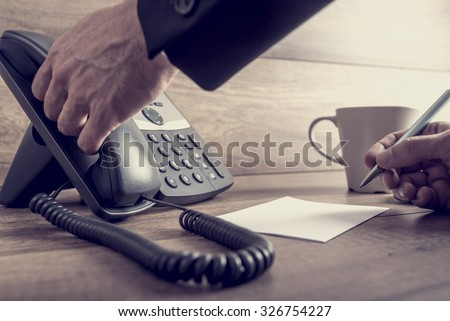 Closeup of male assistant about to answer a telephone call on black landline phone ready to take a message, with a retro filter effect. - stock photo