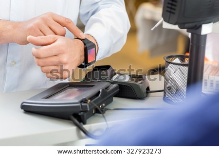 Closeup of male customer paying through smartwatch at counter in pharmacy - stock photo