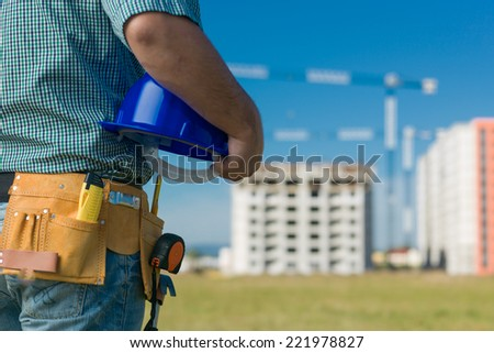 closeup of male engineer holding blue hardhat, with buildings in construction on background - stock photo