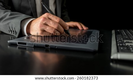 Closeup of male fashion designer sketching and drawing with a stylus pen on graphic tablet. - stock photo