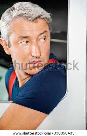 Closeup of male firefighter looking back while reversing firetruck - stock photo