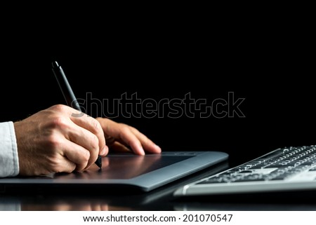 Closeup of male graphic designer working on his digital tablet over black background. - stock photo