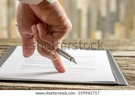 Closeup of male hand holding a pen pointing to a line at the end of a contract, document or application form ready for signature. - stock photo