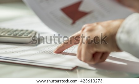 Closeup of male hand pointing to figures written on a document or report in form of statistical data. Conceptual of economy, finance and accounting. - stock photo