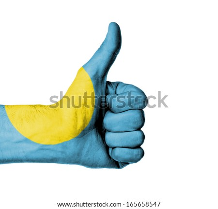 Closeup of male hand showing thumbs up sign, flag of Palau - stock photo