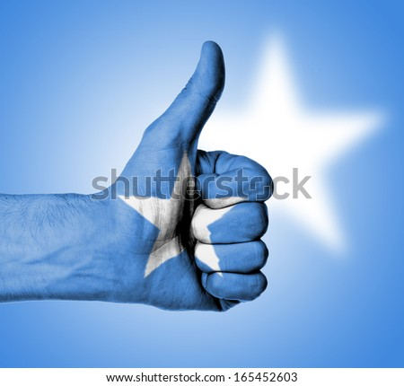 Closeup of male hand showing thumbs up sign, flag of Somalia - stock photo