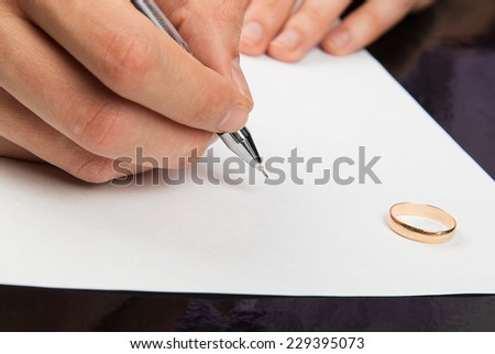 Closeup of male hand signing divorce papers - stock photo