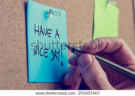 Closeup of male hand writing Have a nice day message on a blue post it paper pinned to a cork bulletin board, toned retro. - stock photo