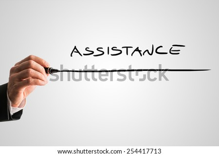 Closeup of male hand writing word Assistance on grey virtual screen. Conceptual of business support, customer care or medical aid and home assistance. - stock photo