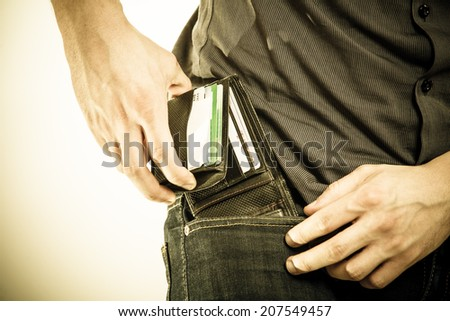 Closeup of male hands. Man taking the wallet out on his pocket. Pay and risk of theft. Isolated on white. Studio shot. Sepia tone. - stock photo